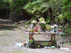 女性の遺体が遺棄された雑木林。献花台には多くの花が手向けられている=26日午後、恩納村安富祖