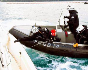 動こうとする抗議船につかまる海上保安官=日午後3時すぎ、名護市辺野古の米軍キャンプ・シュワブ沖