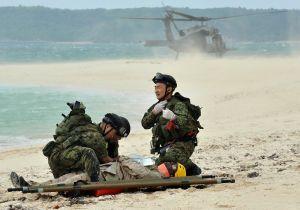 【資料写真】負傷した米兵を自衛隊員が救助する想定の演習。後方は米軍の救難ヘリ=2010年、うるま市・浮原島
