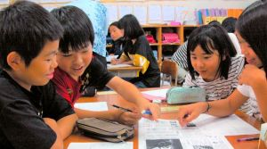 「沖縄全戦没者追悼式」を報じる全国紙の1面を読む児童たち=3日、沖縄市立比屋根小学校