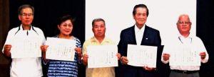 「留年許可」の表彰状を誇らしげに見せる(右から)平田さん、比屋根さん、米須さん、仲村さん、比嘉さん=25日、北中城村・大城区公民館