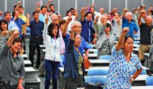 「日本軍の強制」明記を求め、ガンバロー三唱する参加者=29日、浦添市産業振興センター結の街
