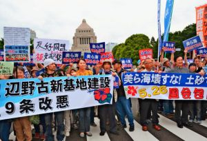 国会を背に、辺野古の新基地建設反対を訴える市民ら=26日、東京都千代田区の国会正門前