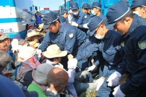 ゲート前に座り込む市民らを排除する県警機動隊員ら=24日午前8時45分、名護市辺野古・米軍キャンプ・シュワブのゲート前