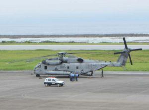 久米島空港に緊急着陸したCH53E大型輸送ヘリ。機体そばでは米兵が警察官に事情聴取されていた=1日午後2時20分ごろ、同空港(又吉嘉例撮影)