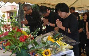 米軍戦闘機墜落事故から59年を迎え、慰霊祭で手を合わせる参加者=30日午前10時すぎ、うるま市立宮森小学校