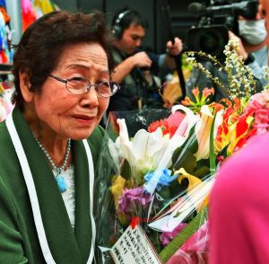 館長退任式で、涙ぐみながら関係者の花束を受け取る島袋淑子さん=30日、糸満市伊原・ひめゆり平和祈念資料館