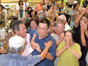 初当選を決め、支持者から祝福される島袋力さん(中央)=9日午後11時20分、名護市・数久田体育館(古謝克公撮影)