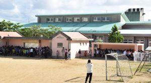 8月末に完成した避難施設(右建物)も使用し、避難訓練する児童ら=12日午前、宜野湾市・普天間第二小学校