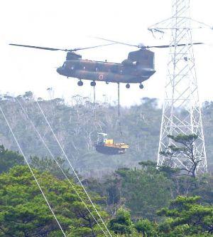 米軍北部訓練場の上空から重機を搬入する陸上自衛隊CH47ヘリ=13日午前9時15分、東村と国頭村の境付近
