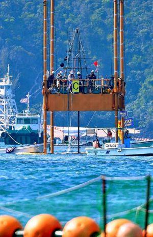 スパット台船にやぐらを設置し、海底ボーリング調査の準備をする作業員=3日午後3時21分、名護市辺野古沖