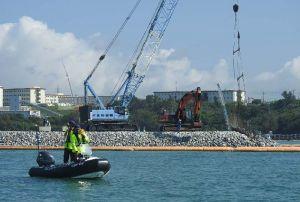 砕石の投下が進む「K4」護岸建設現場と、抗議船の退去を求める船=14日午前9時15分、名護市辺野古の米軍キャンプ・シュワブ沖