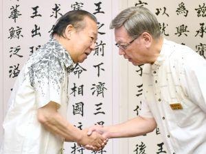 握手を交わす沖縄県の翁長雄志知事(右)と自民党の二階俊博幹事長=14日午前、沖縄県庁