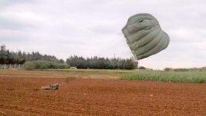 パラシュート降下訓練で、民間地の畑に落下した米兵=10日午前10時43分ごろ、伊江村内(名嘉實さん提供)
