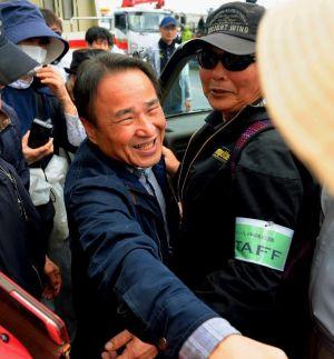 あいさつを終えて集会参加者と握手を交わす山城博治さん