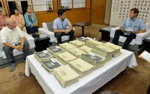 謝花喜一郎副知事(右)に、辺野古新基地建設の是非を問う県民投票の署名と声明を提出した元山仁士郎氏(中央)=5日午前