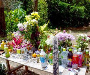 女性が遺棄された恩納村安富祖の県道104号沿いの雑木林。献花台には多くの花が手向けられている=26日