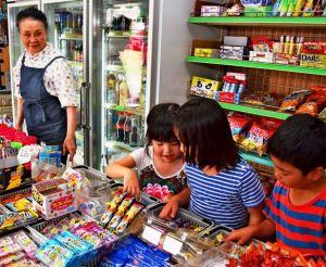 子どもたちのお菓子選びを見守る本永佳子さん(左)=12日、宜野湾市宇地泊の駄菓子屋よっちゃんの店