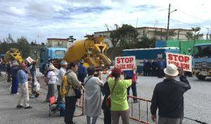 出入りする工事用車両に対し、新基地建設に抗議するプラカードを掲げる市民=27日午後0時10分すぎ、名護市辺野古のキャンプ・シュワブゲート前