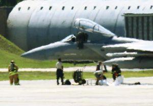 緊急着陸したF15の機体下部に白いシートを広げる作業員や消防隊員ら=25日、米軍嘉手納基地(読者提供)