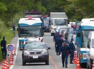 (資料写真)前後を挟む警察車両と、道路脇に立った機動隊員に守られながら砂利を運ぶ工事用トラック=2016年7月26日、東村高江