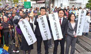 判決を受け、那覇地裁沖縄支部前で垂れ幕を掲げる住民側の弁護士ら=23日午前、沖縄市