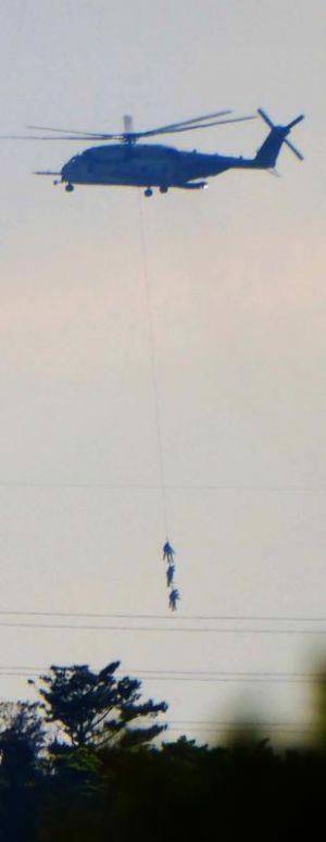 兵士3人をつり下げ、飛行訓練するCH53Eヘリコプター=4日、名護市の上空