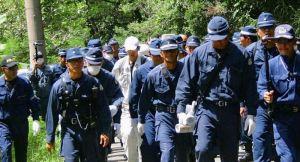 機動隊員に警護され、東村道から北部訓練場に向かうヘリパッド建設工事関係とみられる作業員(中央)=12日、東村高江(仁尾淳史さん提供)