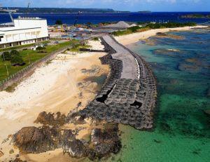護岸工事着手から半年。N5護岸建設予定地近くに造られた作業用の仮設道路が、波打ち際から海に延びる=24日午後、名護市辺野古の米軍キャンプ・シュワブ(小型無人機から)