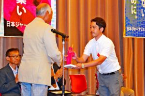 選考委員から受賞トロフィーを受け取る勝浦大輔記者(右)=18日、東京・内幸町の日本プレスセンタービル