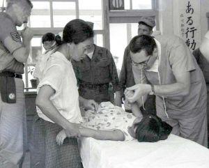 米軍戦闘機墜落後、教室内に急きょ設けられた救急治療室で、児童を手当てする米軍関係の医師(右)と不安げに見守る母親=1959年6月30日