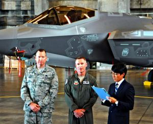F35Aの前で報道陣の質問に答えるジェイソン・ルーシュオフ大佐(中央)とマイケル・マイルズ大佐(左)=7日、米軍嘉手納基地