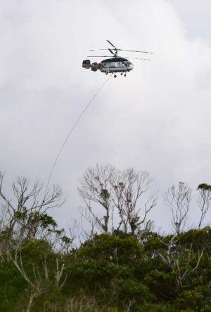 積み荷を下ろしてH地区上空付近を飛ぶ民間ヘリ=14日午前10時43分ごろ、東村高江(提供)