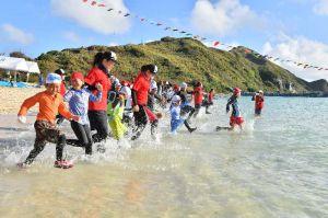 水上運動会がスタートし、一斉に海へ駆け出す参加者=15日午前、渡名喜村・あがり浜(落合綾子撮影)