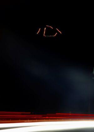 「心」の光文字は国道58号からもはっきり見える=8日午後8時前、名護市城(8秒間露光)