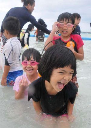 「寒ーい」と声を上げながらも、大はしゃぎする子どもたち=21日、石垣市真栄里・マエサトビーチ