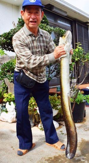 1メートルを超えるオオウナギを捕獲した与古田徳造さん=24日、うるま市みどり町の自宅
