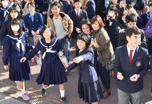 掲示板に自分の番号を見つけ喜ぶ受験生ら=15日午前9時、沖縄市・球陽高校