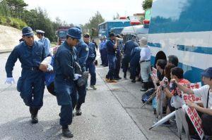 座り込み抗議をしている市民を強制排除する機動隊=15日、名護市辺野古の米軍キャンプ・シュワブゲート前