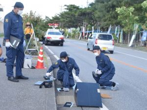 事故現場で鑑識作業する県警職員=24日午前8時40分ごろ、米軍キャンプ・シュワブゲート前
