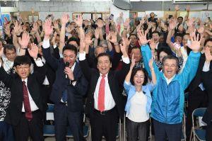 バンザイ三唱で再選を喜ぶ桑江朝千夫氏(中央)=22日午後10時7分、沖縄市久保田の選挙事務所
