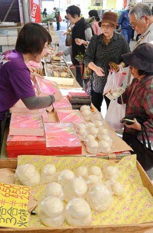 旧正月の餅や菓子などを求める買い物客=15日、糸満市中央市場(田嶋正雄撮影)