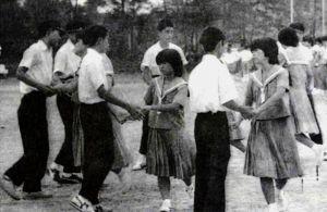1980年代、羽地中学校の運動会でフォークダンスを踊る生徒。「青い山脈」も踊っていたとみられる(「羽地中創立50周年記念誌」より)