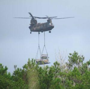 トラックをつり下げて、搬入する陸上自衛隊の大型輸送ヘリCH47=13日午前10時すぎ、東村高江と国頭村安波の境付近