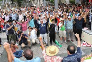 新基地建設反対を訴えガンバロー三唱で気勢を上げる集会参加者=20日午後、那覇市泉崎・県民広場