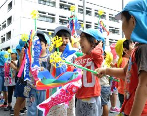 プレゼントされた小さいこいのぼりを手に喜ぶ園児たち=24日、県庁
