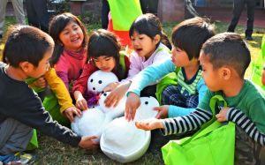 「冷たーい」と雪だるまをさわり喜ぶ園児たち=19日、名護市役所