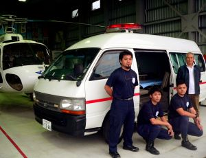赤色灯やサイレンなどを取り付けた手作りの救急車と(写真左から)救急救命士の宮城さん、森元さん、新里さん、整備士の成瀬さん=名護市宇茂佐・メッシュサポートのヘリポート