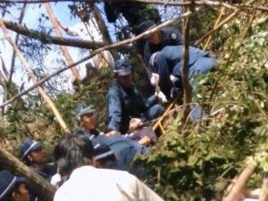 米軍北部訓練場内での抗議行動で、警察官にロープで縛られ引き上げられる市民(中央)=28日(提供)