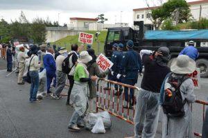 石材などを積んだ工事車両の出入りに抗議する市民ら=12日、名護市辺野古の米軍キャンプ・シュワブ工事車両用ゲート前